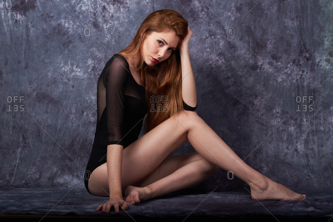 Side view of young slim female with red hair and in black bodysuit sitting on dark background in studio while leaning on hand and looking at camera
