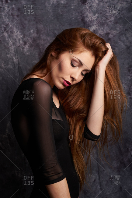 Side view of calm female model in stylish clothes standing with eyes closed in studio with red hair