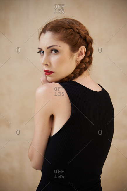 Side view of stylish female model with red hair and braids sitting in studio on dark background and looking at camera