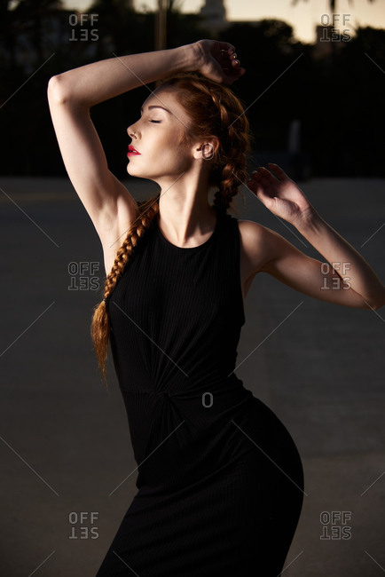 Slender stylish female model with braids and in black dress standing in street with eyes closed