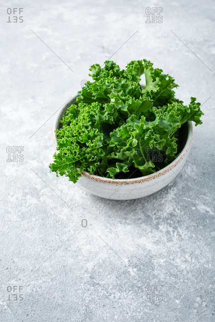 Overhead view of kale in bowl on light surface