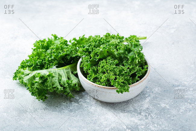 Fresh green kale leaves on light surface