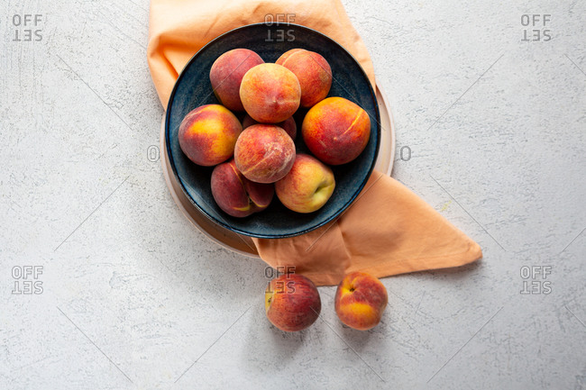 Overhead view of peaches in bowl and cloth on light surface