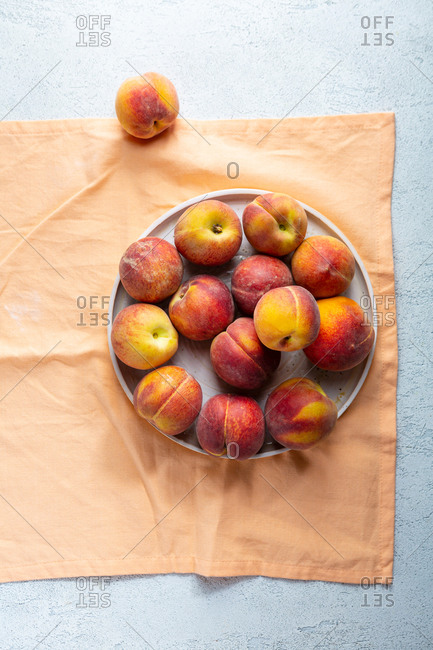 Overhead view of peaches on plate on orange textile
