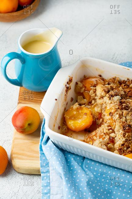 Close up of peach granola crumble breakfast with custard
