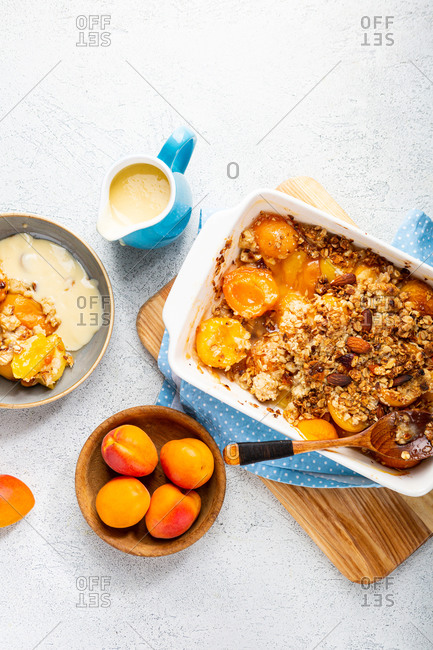 Peach granola crumble with custard and almond in white baking dish