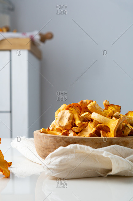 Wild mushrooms in wooden bowl on white table
