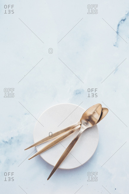 Golden spoons on a dish on light marble surface