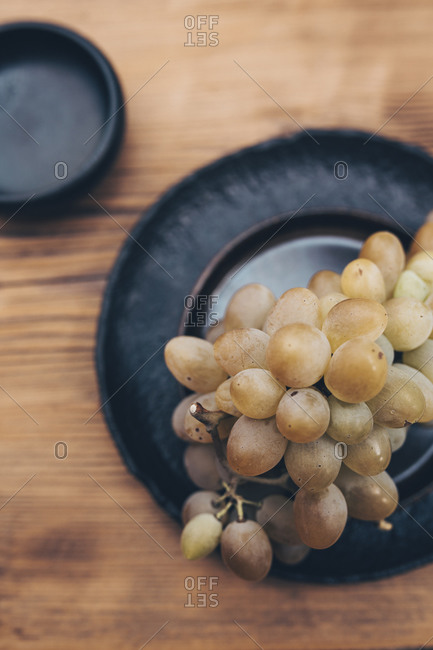 Bunch of white grapes on a black plate against wooden background