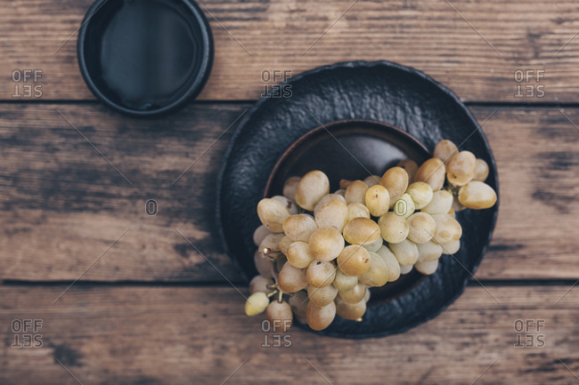 Overhead view of a bunch of white grapes on a black plate against wooden background