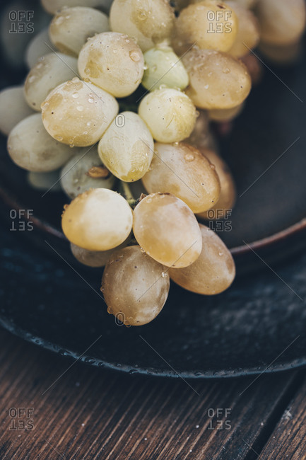 Close up of a white grape bunch on a black plate