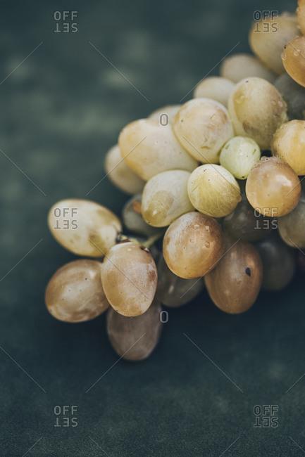 Close up of a bunch of white grapes on a dark green background