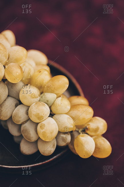 Bunch of white grapes on a dark plate against burgundy background