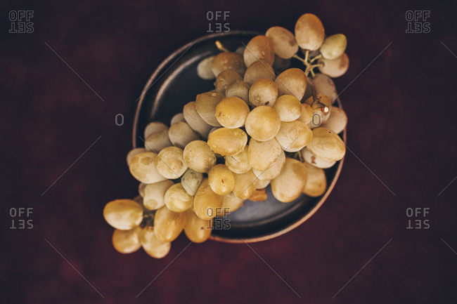 Top view of bunch of white grapes on a dark plate against burgundy background