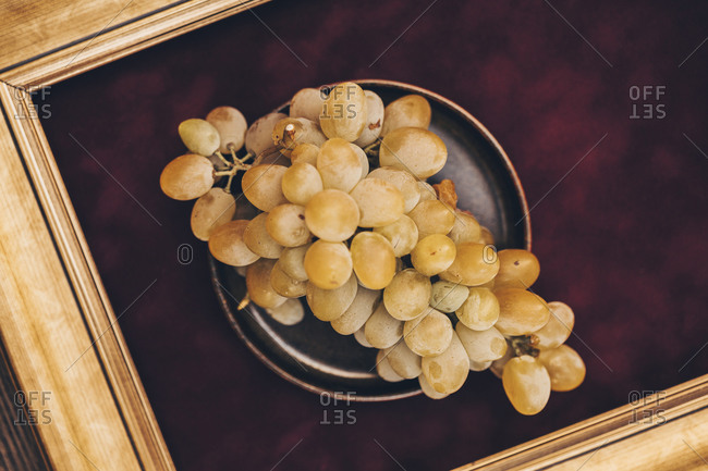 Overhead view of bunch of white grapes on a dark plate against burgundy background with frame