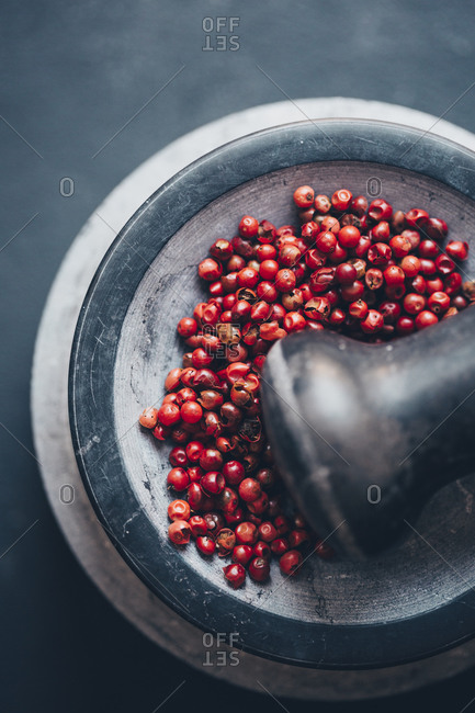 Mortar with dried red peppercorns on gray surface