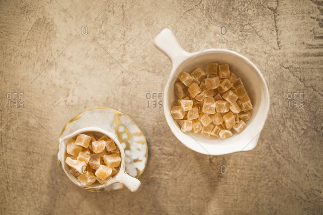 Overhead view of candied ginger pieces in ceramic bowl against stone background