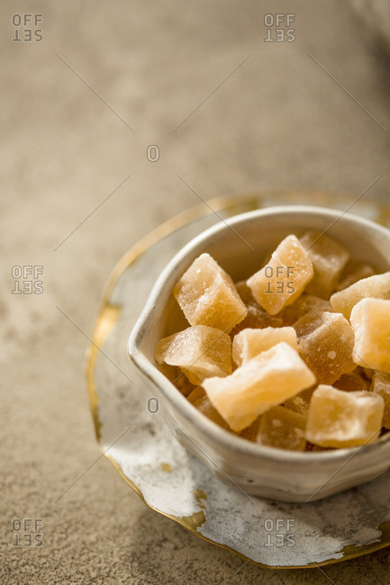 Candied ginger pieces in ceramic bowl against stone background