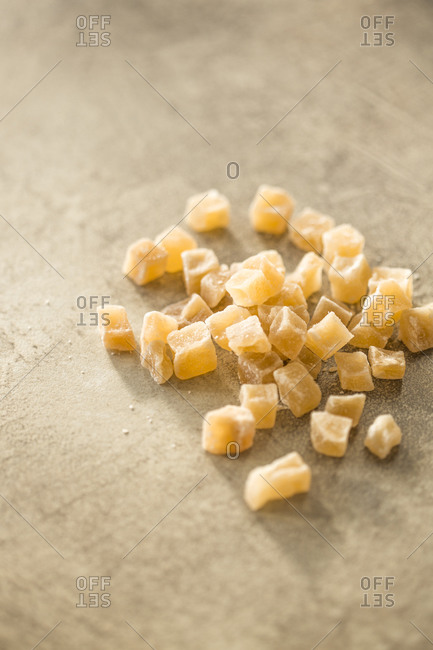 Candied ginger pieces on a stone background