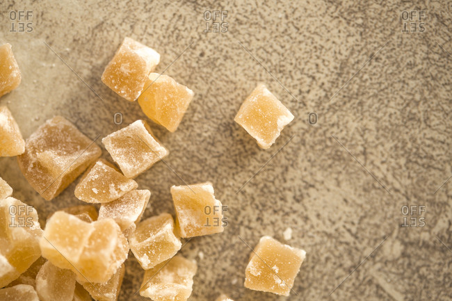 Close up of candied ginger pieces on a stone background
