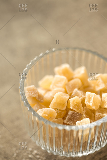 Candied ginger pieces in glass bowl against stone background