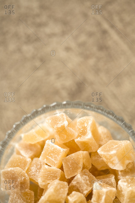 Top view of candied ginger pieces in glass bowl against stone background