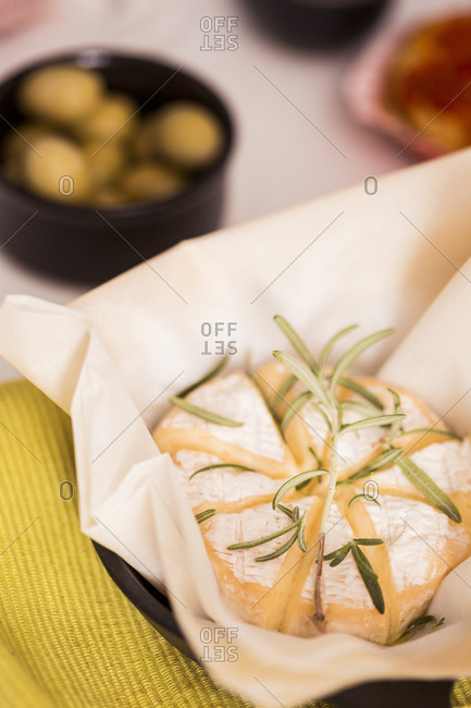 Baked camembert cheese with rosemary sprigs on table
