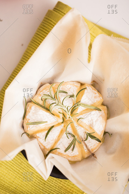 Overhead view of baked camembert cheese with rosemary sprigs on table