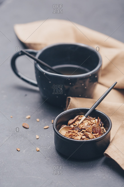 Homemade granola in black bowl with tea on a table