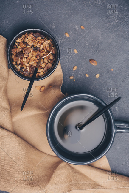 Overhead view of homemade granola in black bowl with tea on a table