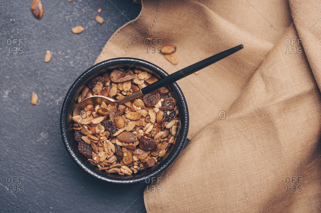 Homemade granola in black bowl on table viewed from above