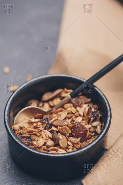 Close up of homemade granola in black bowl on table