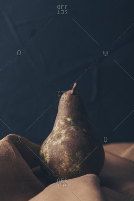 Pear with freckles on ocher cloth against black background