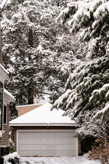 Fresh snowfall over a residential home's garage and tall trees