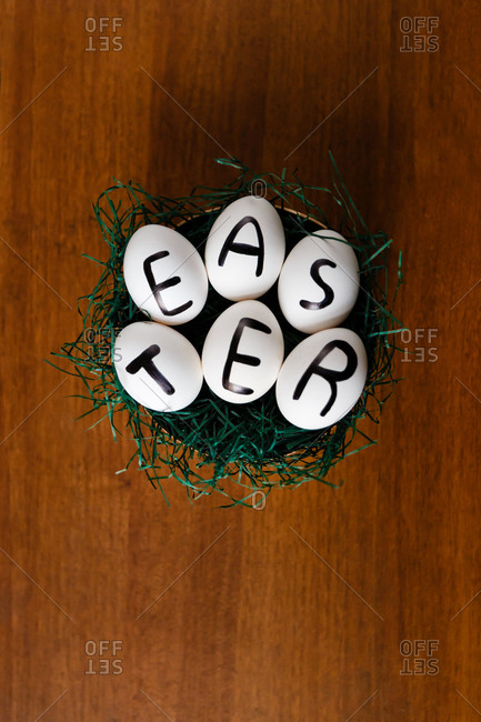 Chicken eggs with Easter written on them in a nest with grass on a wooden background