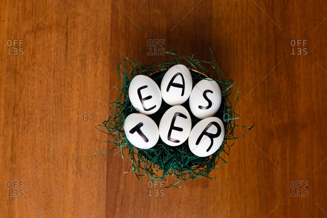 Eggs with Easter written on them in a nest with grass on a wooden background