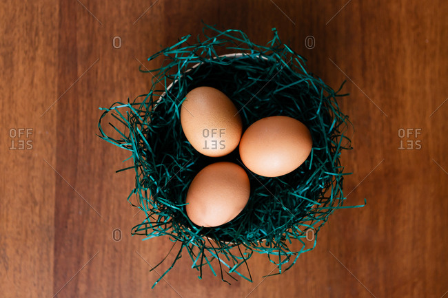 Overhead view of chicken eggs in a nest with grass on a wooden background