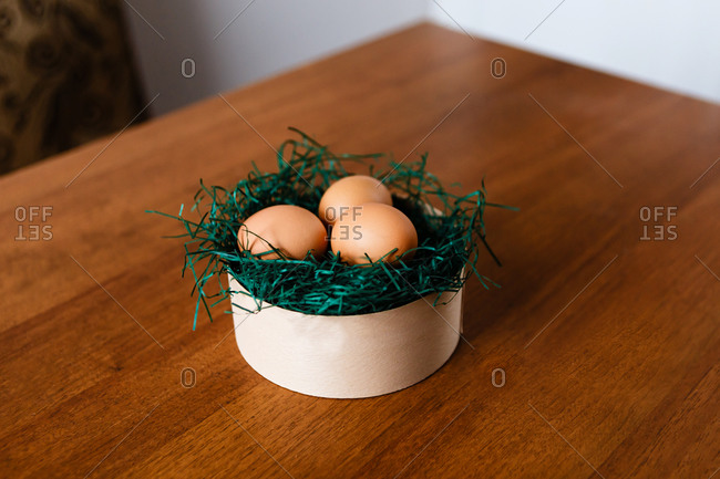 Brown chicken eggs in a nest with grass on a wooden background