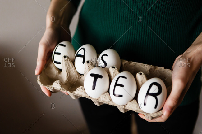 Hands holding chicken eggs with Easter written on them in a package made of recycled paper