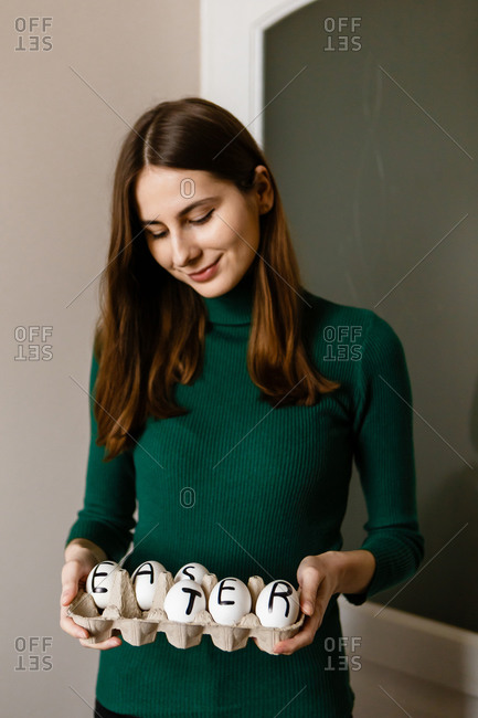 Woman holding chicken eggs reading Easter in a recycled paper package and smiling