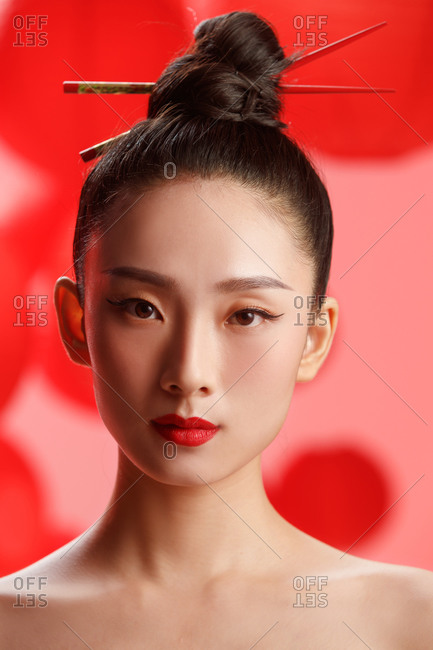 Headshot of an Asian female model against red background