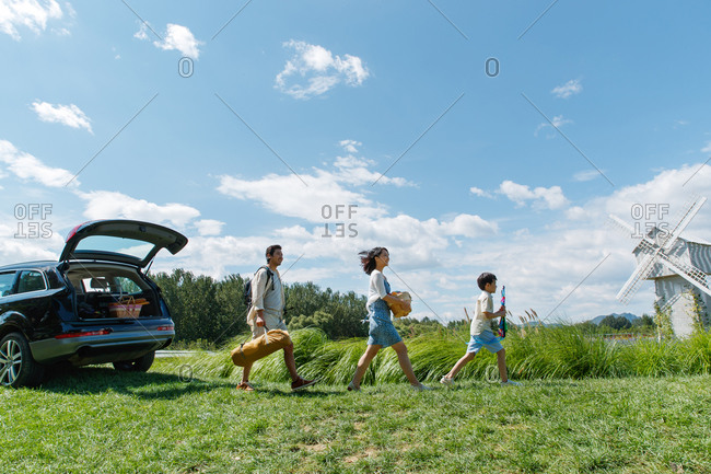 Happy family unloading car for a picnic outing in field with windmill in the background
