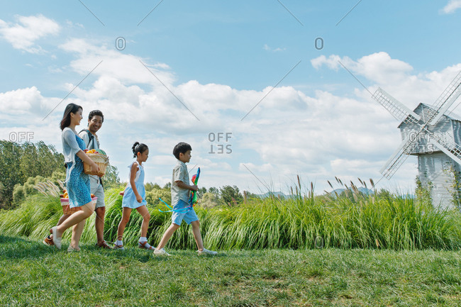 Happy family walking with picnic items in a field with windmill in the background