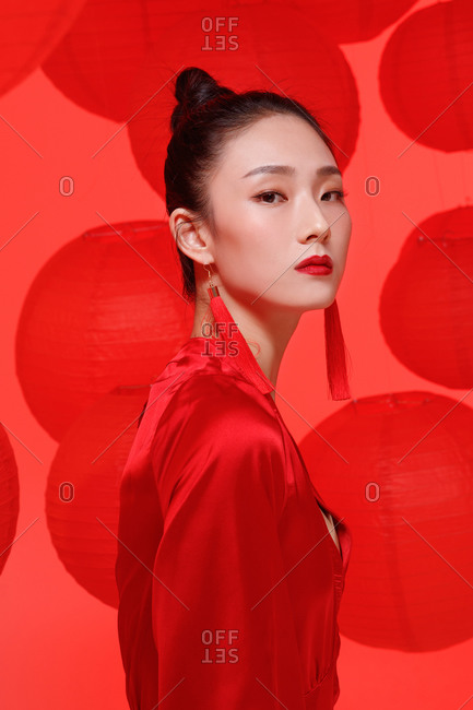 Profile view of a female Chinese model wearing red against a backdrop of red lanterns
