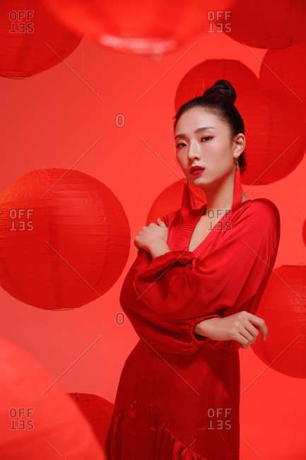 Female Chinese model posing in red against a backdrop of red lanterns