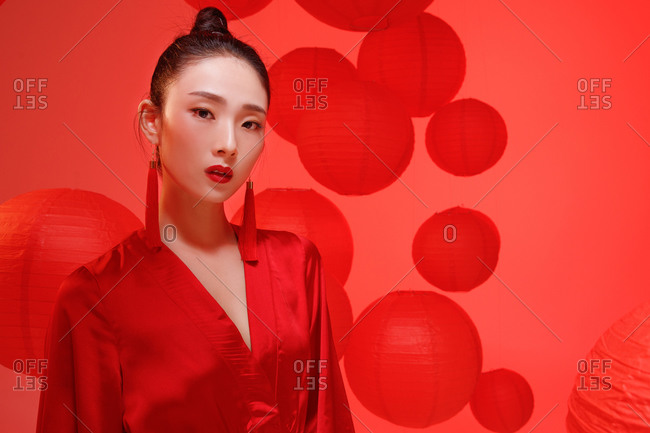 Beautiful female Chinese model posing in red against a backdrop of red lanterns