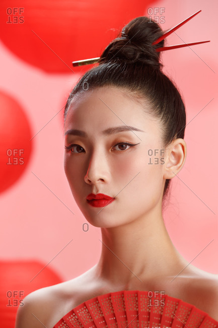 A pretty female Chinese model posing in red against a backdrop of red lanterns