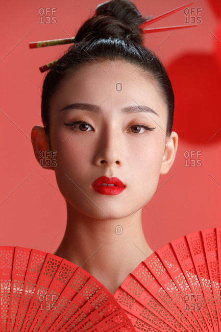 Close up of a beautiful female Chinese model posing in red against a backdrop of red lanterns