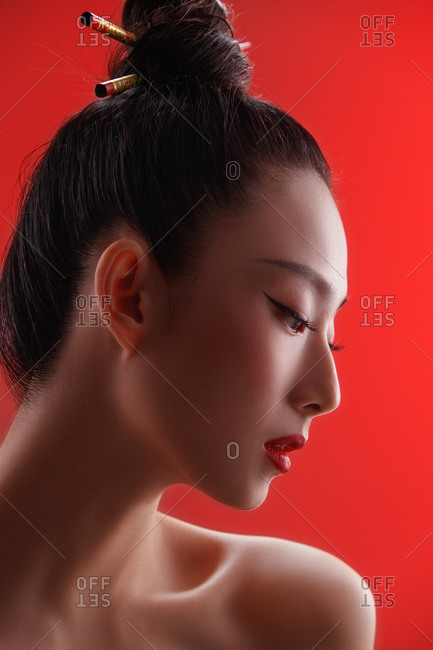 Profile view of a beautiful female Chinese model posing in red against a red backdrop