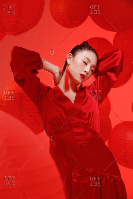 Pretty Asian female model standing with hands behind her neck against red background with lanterns